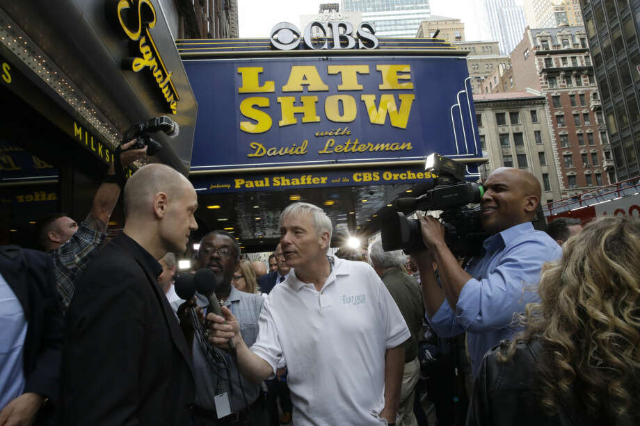 "An audience member of the final taping of the CBS ""Late Show with David Letterman"" speaks to a reporter outside the Ed Sullivan Theater in New York, Wednesday, May 20, 2015. Letterman signed off Wednesday after 33 years and 6,028 broadcasts of his late-night show. (AP Photo/Mary Altaffer)"