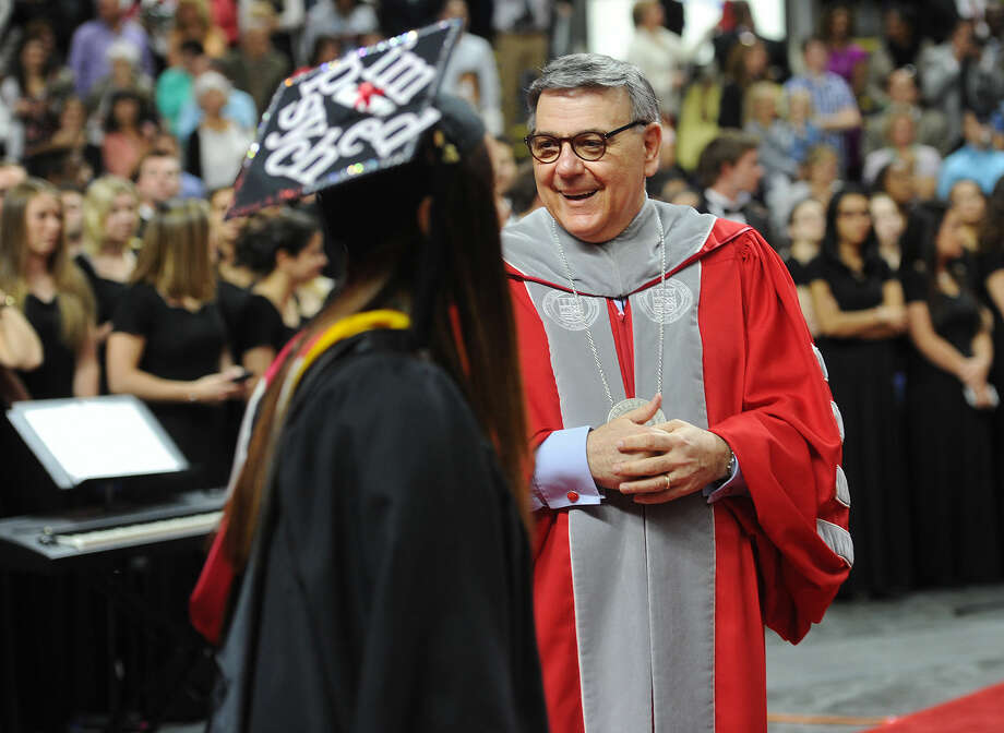 Sacred Heart University President John J. Petillo greets graduates as they march in to Sacred Heart University's graduation at the Webster Bank Arena in Bridgeport, Conn. on Sunday, May 15, 2016.