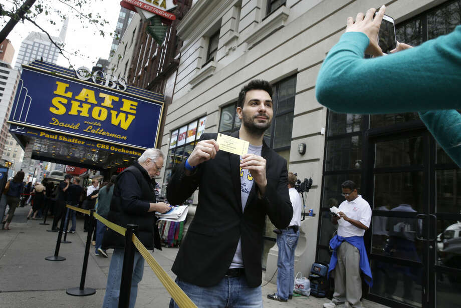 Matt Demers, of Ottawa, Canada, poses for a picture with his ticket to David Letterman's last show outside the Ed Sullivan Theater in New York, Wednesday, May 20, 2015. After 33 years and 6,028 broadcasts of his late-night show, David Letterman is retiring. (AP Photo/Seth Wenig)