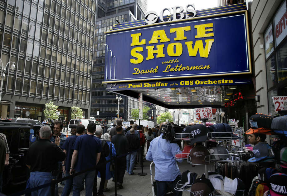 People gather under the marquee of the Ed Sullivan Theater in New York, Wednesday, May 20, 2015. After 33 years and 6,028 broadcasts of his late-night show, David Letterman is retiring. (AP Photo/Seth Wenig)