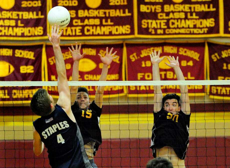 St. Joseph's Pat Thompson, center, and teammate Connor Rodriguez, right, go up to block a spike by Staples' Daniel Brill during boys volleyball action in Trumbull, Conn. on Friday May 13, 2016.