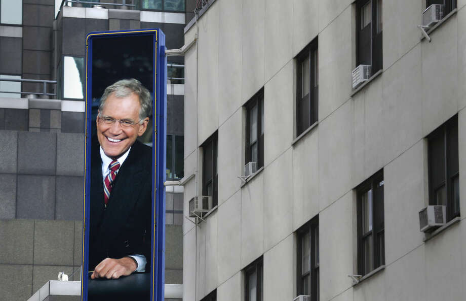 A picture of David Letterman hangs outside the Ed Sullivan Theater in New York, Wednesday, May 20, 2015. After 33 years and 6,028 broadcasts of his late-night show, David Letterman is retiring. (AP Photo/Seth Wenig)