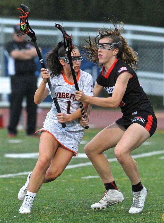 Ridgefield's Kaitlyn McMullan (1) is defended by Fairfield-Ward's Libby McKenna (14) in the girls lacrosse game between Fairfield-Ward and Ridgefield high school, on Friday night, May 13, 2016, at Ridgefield High School, in Ridgefield, Conn.