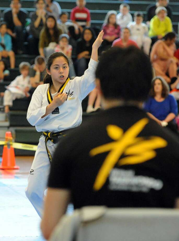 Valeria Carias competes along with her teammates Aditya Chawdraker and Aaron Liebskind in the Team Form competition of the YB World Taekwondo Academy championship tournament at Rippowam Middle School in Stamford on May 14, 2016. Carrias, Chawdraker and Liebskind, all Black Belts, took first place for Team Form in the Children Black Belt division.