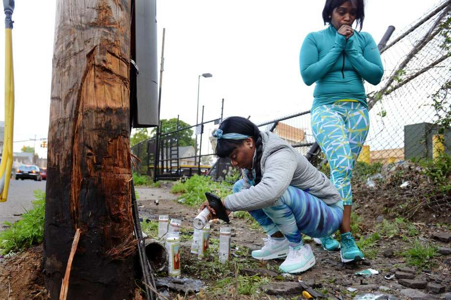 Farrah Boston lights candles at the scene of a fatal car accident on Bishop Avenue in Bridgeport on Saturday. At right is Tamara Dyce, who was engaged to Bridgeport firefighter Jimmie Jones, who died in the accident.