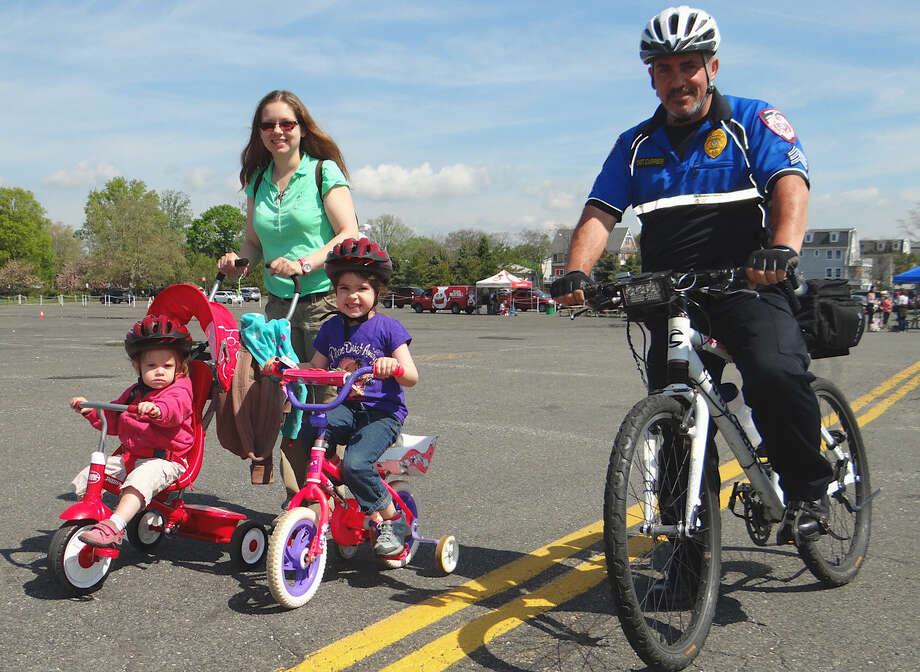 Fairfield University Sgt. David Currier joins Maryann Petrone, of Fairfield, and daughters Sophie and Madeline, ages 2 and 5, at on the Bike Rodeo course.