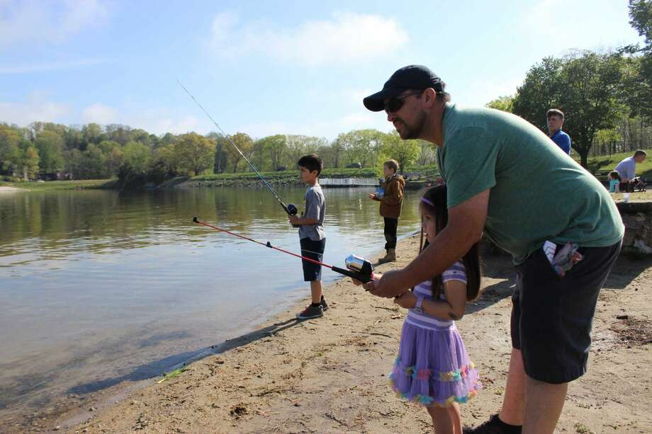 Max Goicoechea helps his daughter Martina, 4, cast a line at the Danbury Fish & Game Association's 45th annual Kid's Fishing Derby held at Candlewood Town Park in Danbury on Sat., May 14, 2016.