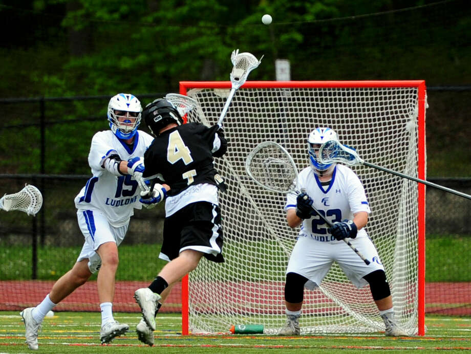 Trumbull's Danny Hoffmann attempts a goal shot as Fairfield Ludlowe's Joseph Casucci, left, and goalie Carter Leibrock defend during boys lacrosse action in Fairfield, Conn., on Saturday May 14, 2016.