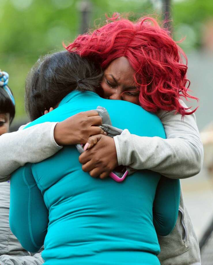 Tameka King, facing camera, comforts her cousin, Tamara Dyce, at the scene of a fatal car accident on Bishop Avenue in Bridgeport on Saturday. Bridgeport firefighter Jimmie Jones, who died in the accident, was engaged to Dyce.