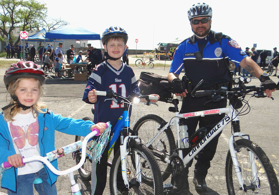 Fairfield University Officer Rick Santiago escorts Amber and Colm Watcke, 5 and 8, of Fairfield, around a safety course at Fairfield PAL's Bicycle Rodeo.