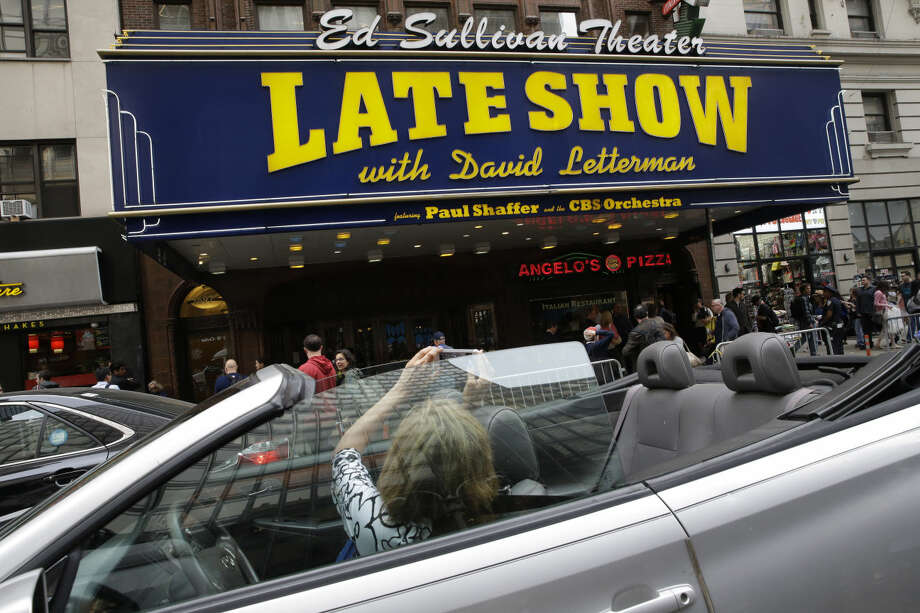 "A woman takes a photo of the CBS ""Late Show with David Letterman"" marquis of the Ed Sullivan Theater in New York, Wednesday, May 20, 2015. Letterman signed off Wednesday after 33 years and 6,028 broadcasts of his late-night show. (AP Photo/Mary Altaffer)"