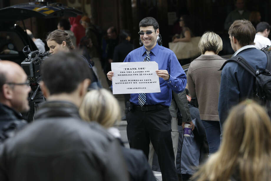 "A fan holds a sign outside the CBS ""Late Show with David Letterman"" at the Ed Sullivan Theater in New York, Wednesday, May 20, 2015. Letterman signed off Wednesday after 33 years and 6,028 broadcasts of his late-night show. (AP Photo/Mary Altaffer)"