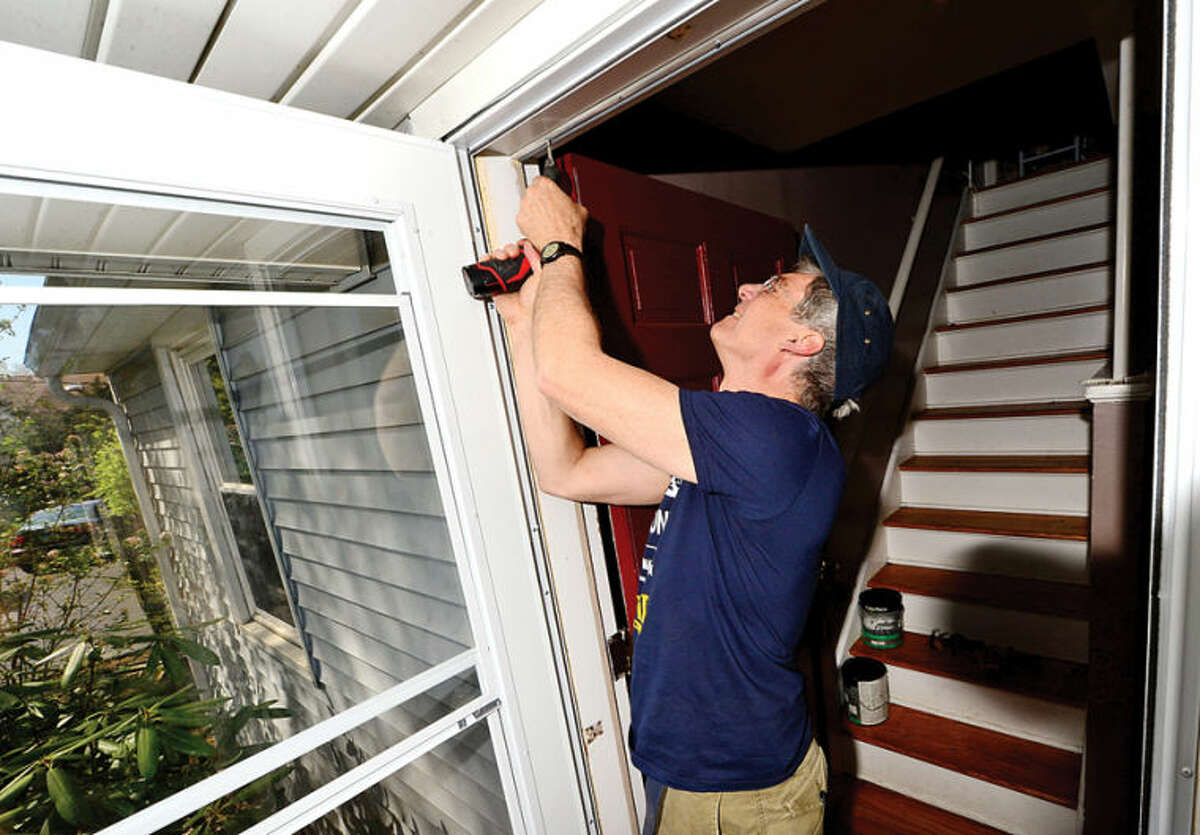 """""""This Old House"""" volunteer Tom Baker fixes a doorway at a home on Walter Avenue in Norwalk for HomeFront Day in this file photo."""