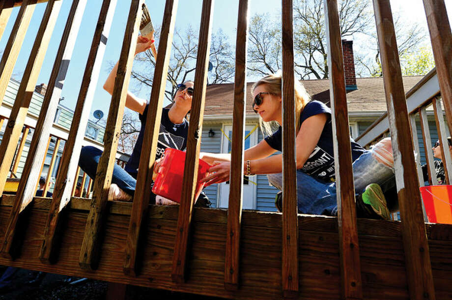 """This Old House"" volunteer Kayla Gambino and Kelly large paint a deck at a home on Walter Avenue in Norwalk for HomeFront Day in this file photo."