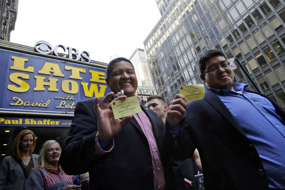 "Audience members of the final taping of the CBS ""Late Show with David Letterman"" display their tickets as they leave the Ed Sullivan Theater in New York, Wednesday, May 20, 2015. Letterman signed off Wednesday after 33 years and 6,028 broadcasts of his late-night show. (AP Photo/Mary Altaffer)"