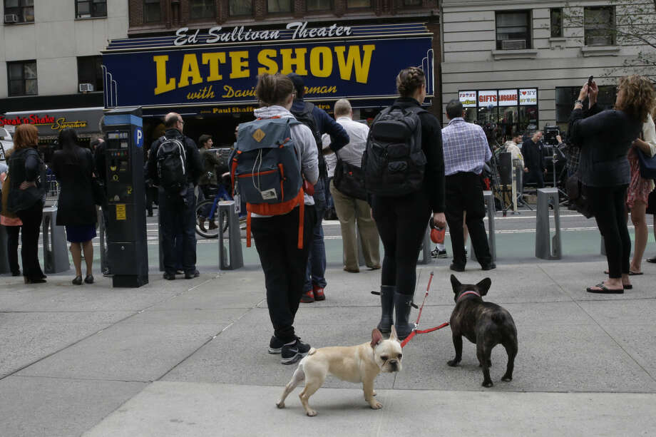 "People assemble outside the Ed Sullivan Theater in New York during the final taping of the CBS ""Late Show with David Letterman,"" Wednesday, May 20, 2015. Letterman signed off Wednesday after 33 years and 6,028 broadcasts of his late-night show. (AP Photo/Mary Altaffer)"