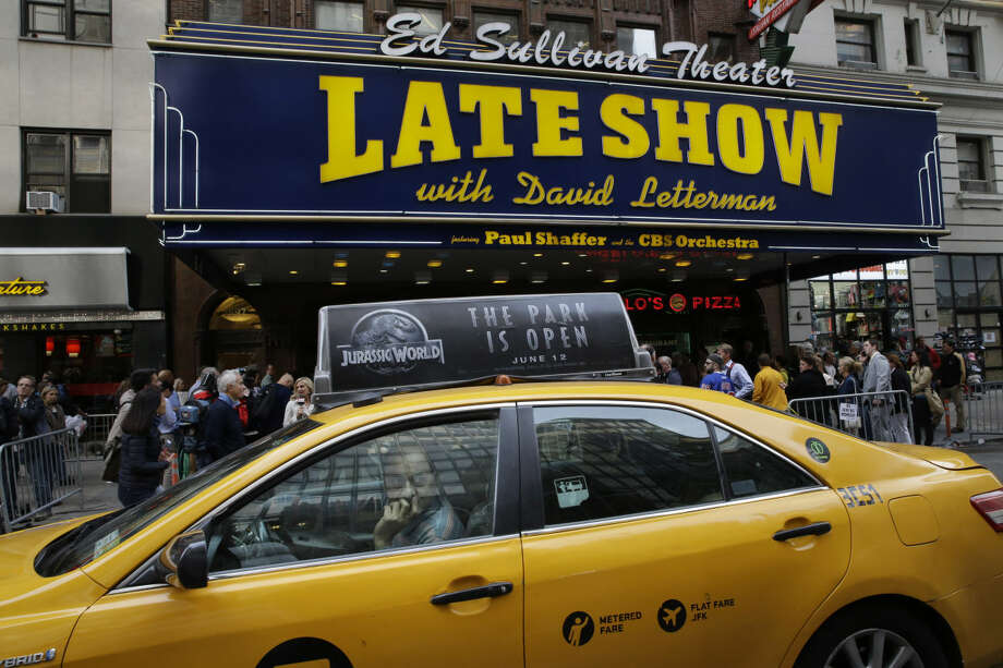 "A cab driver watches the media that is set up across the street from the Ed Sullivan Theater in New York, ahead of the final taping of the CBS ""Late Show with David Letterman,"" Wednesday, May 20, 2015. Letterman signed off Wednesday after 33 years and 6,028 broadcasts of his late-night show. (AP Photo/Mary Altaffer)"