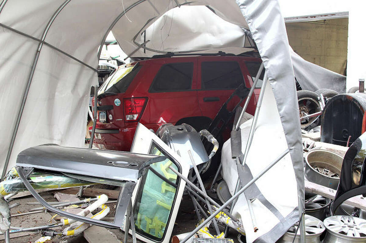 Hour photo / Chris Bosak A Jeep Laredo crashed into the back of Marty's Auto Body on Cross Street in Norwalk on Monday evening. No one was seriously injured.