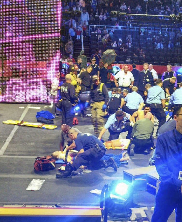 In this photo provided by Rose Viveiros, first responders work at the center ring after a platform collapsed during an aerial hair-hanging stunt at the Ringling Brothers and Barnum and Bailey Circus, Sunday, May 4, 2014, in Providence, R.I. At least nine performers were seriously injured in the fall, including a dancer below, while an unknown number of others suffered minor injuries. (AP Photo/Rose Viveiros) MANDATORY CREDIT