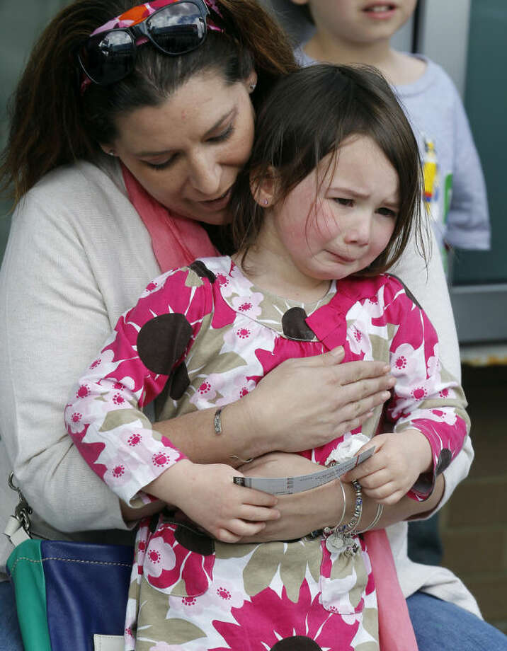 Stacey Tracy, of Cranston, R.I., comforts her daughter Emily Tracy, 4, after she found out the 3:00 p.m. show of the Ringling Bros. and Barnum & Bailey Circus had been canceled, Sunday, May 4, 2014, in Providence, R.I. A platform collapsed during an aerial hair-hanging stunt at the 11 a.m. performance Sunday, sending eight acrobats plummeting to the ground. At least nine performers were seriously injured in the fall, including a dancer below, while an unknown number of others suffered minor injuries. (AP Photo/Stew Milne)
