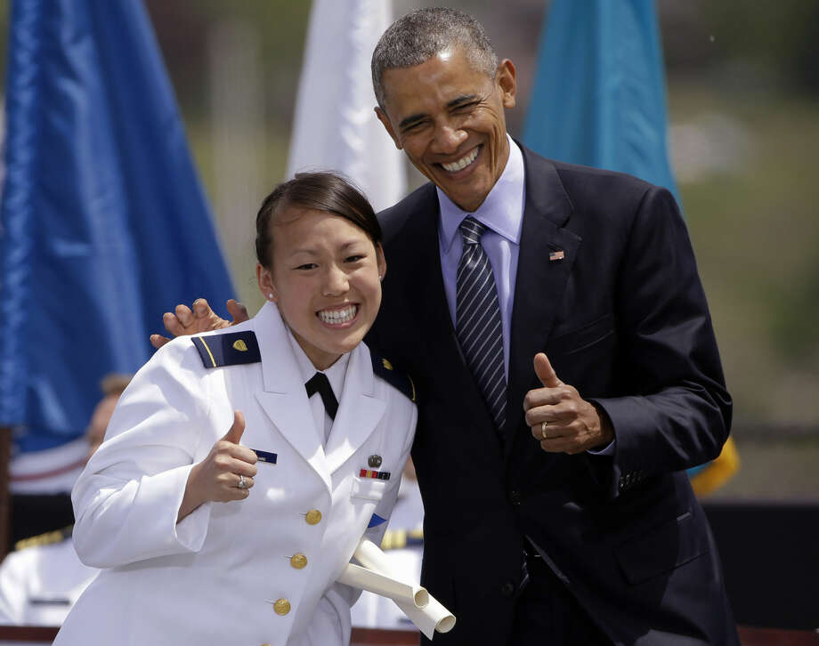 President Barack Obama flashes a thumbs-up with newly commissioned Ensign Ellie Wu at the U.S. Coast Guard Academy's 134th Commencement Exercises, Wednesday, May 20, 2015, in New London, Conn. Obama delivered the commencement address before presenting the graduates with their commissions. (AP Photo/Stephan Savoia)