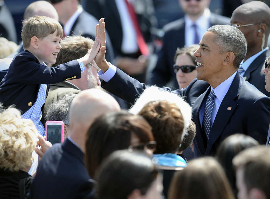 President Barack Obama high-fives Trey Vance, 5, of Waterbury, Conn. after arriving at Groton-New London Airport, Wednesday, May 20, 2015, in Groton, Conn. Tomorrow is Vance's sixth birthday. The president is in Connecticut to give the commencement address at the Coast Guard Academy. (AP Photo/Jessica Hill)