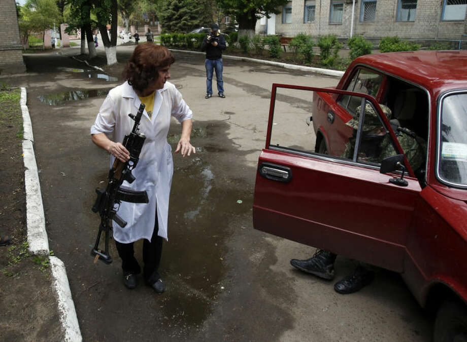 A nurse holds a gun as she helps a wounded Pro-Russian gunmen to get out of the car in front of local hospital in Slovyansk, eastern Ukraine, Monday, May 5, 2014. Ukrainian troops fought pitched gun battles Monday with a pro-Russia militia occupying an eastern city — an apparent escalation of their efforts to bring the region back under government control. (AP Photo/Darko Vojinovic)