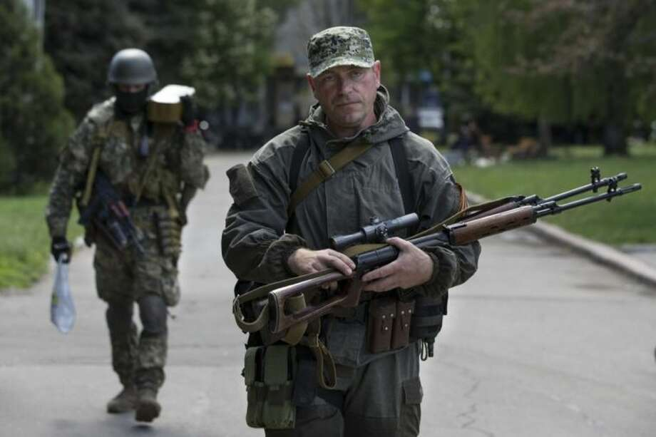 Pro-Russian gunmen carry their weapons at the local administration building in the center of Slovyansk, Ukraine, Tuesday, May 6, 2014. Gunbattles took place at various positions around the city Monday in what has proven the most ambitious government effort to date to quell unrest in the mainly Russian-speaking east. (AP Photo/Alexander Zemlianichenko)