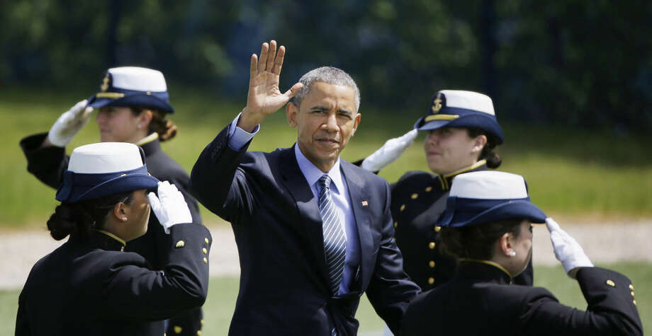 President Barack Obama waves as he walks through a group of saluting second-year cadets as he arrives at the U.S. Coast Guard Academy's 134th Commencement Exercises, Wednesday, May 20, 2015 in New London, Conn. Obama spoke on global warming during his commencement address. (AP Photo/Stephan Savoia)
