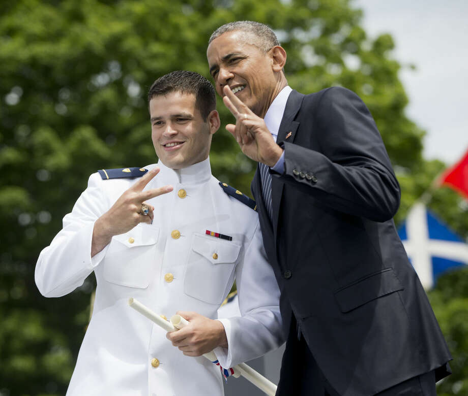President Barack Obama and Ensign Javier Paula flash a 'peace' gesture after he received his diploma and commission at the U.S. Coast Guard Academy, Wednesday, May 20, 2015, graduation in New London, Conn. (AP Photo/Pablo Martinez Monsivais)