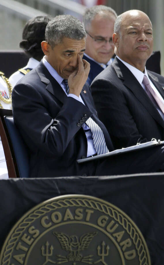 President Barack Obama, sitting next to Homeland Security Secretary Jeh Johnson, rubs his eye as he looks over his speech before delivering the commencement address at the U.S. Coast Guard Academy's 134th Commencement Exercises, Wednesday, May 20, 2015, in New London, Conn. (AP Photo/Stephan Savoia)