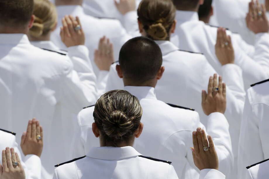 First-year cadets raise their hands as they take the oath of newly commissioned ensigns at the U.S. Coast Guard Academy's 134th Commencement Exercises, Wednesday, May 20, 2015, in New London, Conn. where President Barack Obama delivered the commencement address speaking on global warming. (AP Photo/Stephan Savoia)