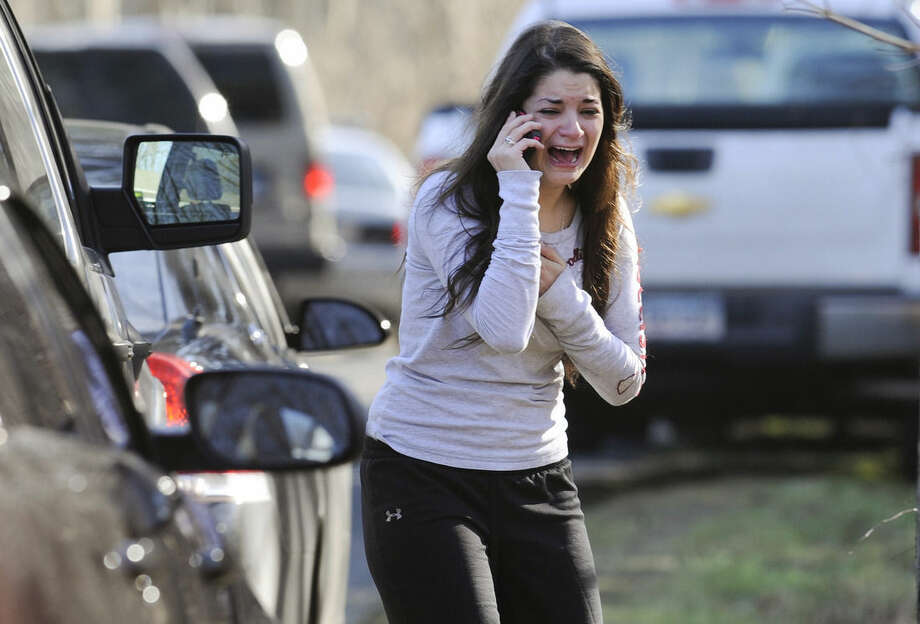 FILE - In this Dec. 14, 2012, file photo, Carlee Soto uses a phone to get information about her sister, Victoria Soto, a teacher at the Sandy Hook elementary school in Newtown, Conn., after a gunman killed over two dozen people, including 20 children. Victoria Soto, 27, was among those killed. U.S. public schools beefed up security measures with safety drills and parent notification systems in the years surrounding the massacre at Connecticut's Sandy Hook Elementary School, according to a government survey released Thursday, May 21, 2015. (AP Photo/Jessica Hill, File)