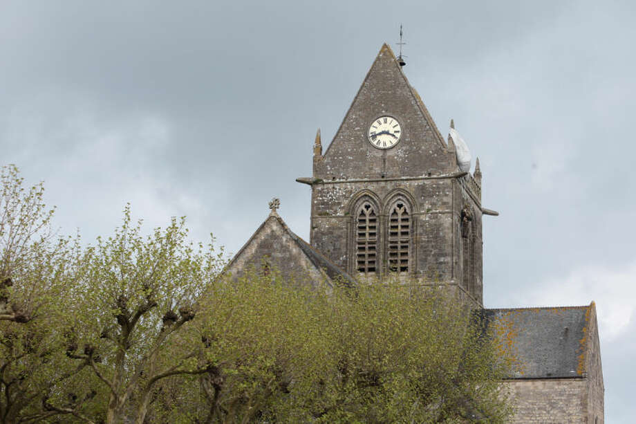 This April 25, 2014 photo shows a mannequin hanging on the Belltower of Sainte Mere Eglise, representing a WWII paratrooper from the 82nd Airborne in Sainte Mere Eglise, western France. Local officials estimate that several hundred thousand tourists will flock to Normandy this summer, attracted by the 70th anniversary of D-Day. (AP Photo/David Vincent)