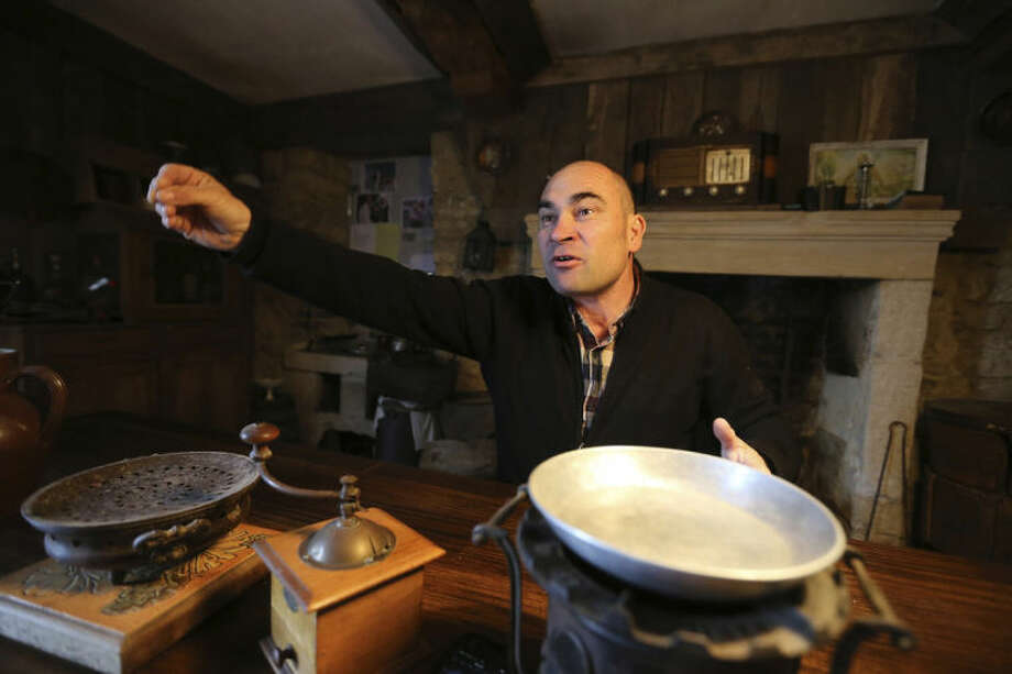 """This April 25, 2014 photo shows bakery supply salesman and amateur D-Day historian Sebastien Olard, 46, owner of the """"House of the Liberation"""", first house liberated by American soldiers on June, 6, 1944, in Saint Laurent sur Mer, western France. Local officials estimate that several hundred thousand tourists will flock to Normandy this summer, attracted by the 70th anniversary of D-Day. The commemorations culminate on June 6 in the port of Ouistreham, where U.S. President Barack Obama, French president Francois Hollande and Britain's Queen Elizabeth II will gather to remember the more than 9,000 Allied soldiers killed or wounded that day. (AP Photo/David Vincent)"""