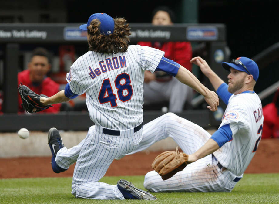 Jayson Heyward's second-inning foul ball drops between New York Mets starting pitcher Jacob deGrom (48) and Mets third baseman Eric Campbell (29) in a baseball game against the St. Louis Cardinals in New York, Thursday, May 21, 2015. (AP Photo/Kathy Willens)