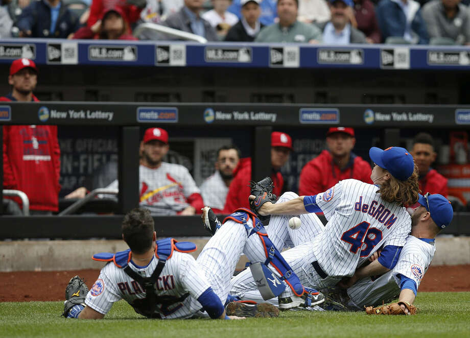 Jayson Heyward's second-inning foul ball drops between New York Mets catcher Kevin Palwecki, left, starting pitcher Jacob deGrom (48) and Mets third baseman Eric Campbell, right, in a baseball game against the St. Louis Cardinals in New York, Thursday, May 21, 2015. (AP Photo/Kathy Willens)