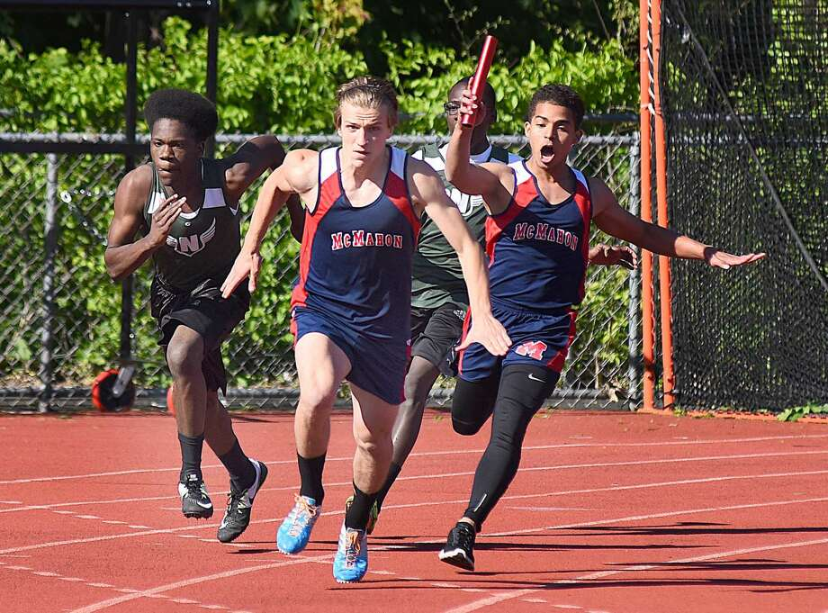 Brien McMahon's Niko Petridis, front, gets ready to receive the relay baton from teammate Winston Cabrera Arias, right, en route to their 4x100 relay win against Norwalk on Monday.