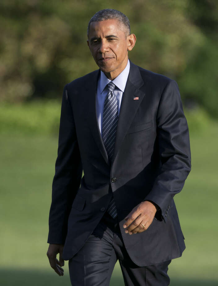 President Barack Obama walks across the South Lawn to the White House from Marine One, Wednesday, May 20, 2015, in Washington, as he returns from Connecticut where he delivered the commencement address at the United States Coast Guard Academy and attended a Democratic National Committee event. (AP Photo/Carolyn Kaster)