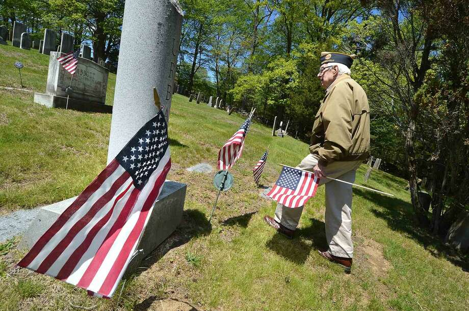 American Legion Post 86 members and Veterans Raymond Tobiasen, Past Commander Bing Ventres and Judd Mott, place new American Flags on veterans markers and remove the old ones at Hillside Cemetery for Memorial Day in Wilton. The Post pays for and donates some 400 flags for Veterans in five Wilton cemeteries, in Wilton Conn. Monday May16, 2016