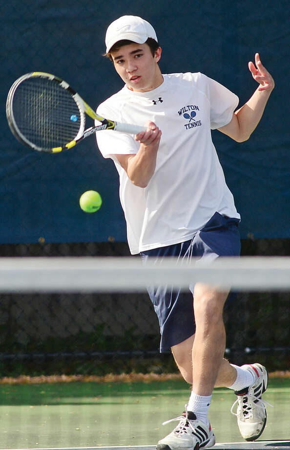 Hour photo / Erik Trautmann Wilton High School's #2 single Ian Erickson plays Staples' William Andrew during their FCIAC Boys Tennis final in Westport Thursday.