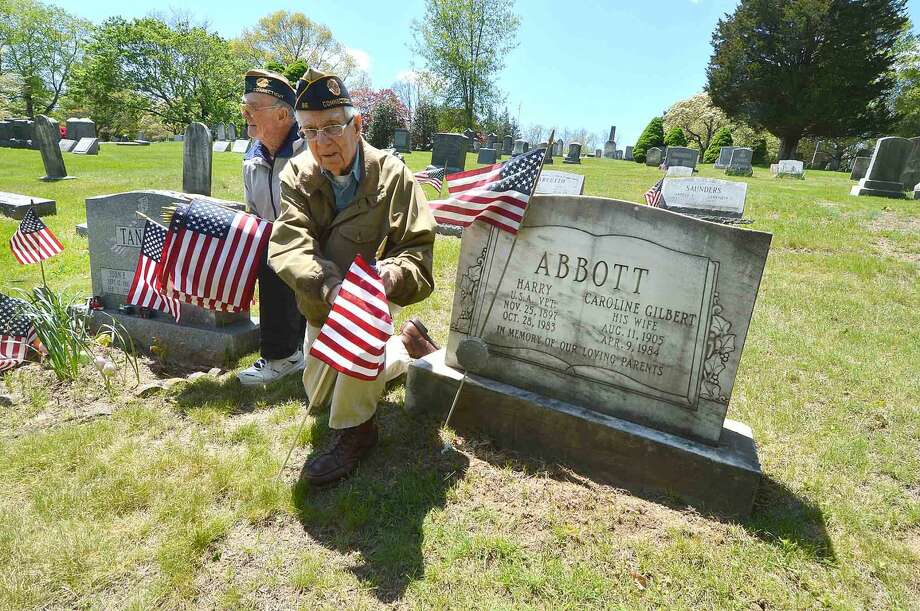 American Legion Post 86 Past Commander Bing Ventres and Judd Mott, place new American Flags on veterans markers and remove the old ones at Hillside Cemetery for Memorial Day in Wilton. The Post pays for and donates some 400 flags for Veterans in five Wilton cemeteries