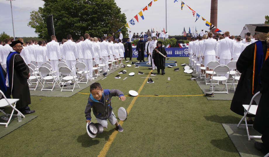 A young boy runs off with a cadet's hat after the newly commissioned ensigns tossed them into the air at the conclusion at the U.S. Coast Guard Academy's 134th Commencement Exercises during the closing procession, Wednesday, May 20, 2015, in New London, Conn. where President Barack Obama delivered the commencement address speaking on global warming. (AP Photo/Stephan Savoia)