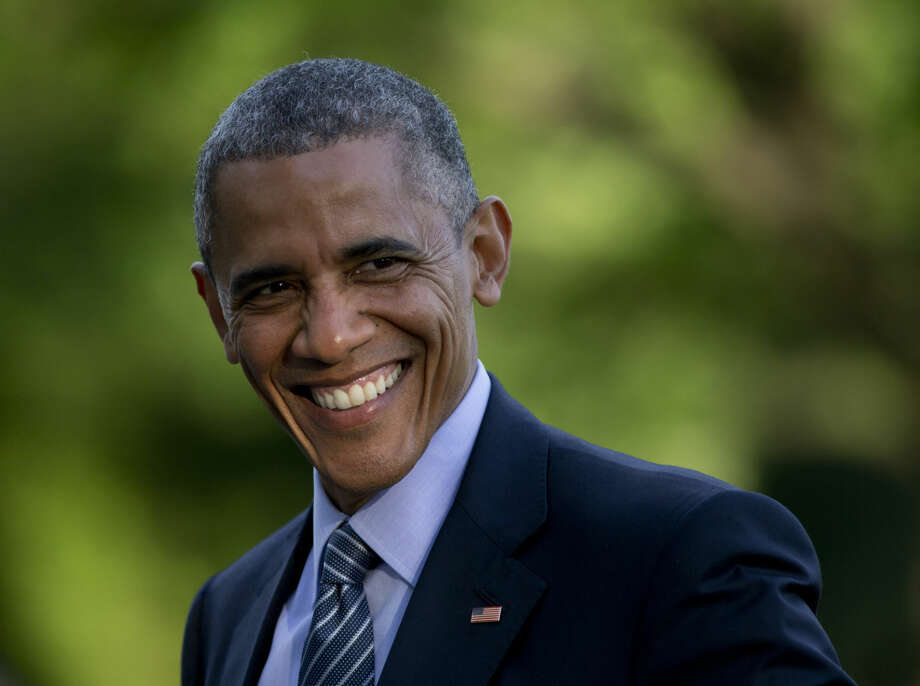 President Barack Obama smiles as he walks across the South Lawn to the White House from Marine One, Wednesday, May 20, 2015, in Washington, as he returns from Connecticut where he delivered the commencement address at the United States Coast Guard Academy and attended a Democratic National Committee event. (AP Photo/Carolyn Kaster)