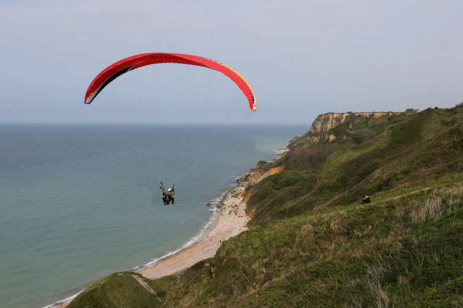 This April 24, 2014 photo shows people paragliding over the D-Day beaches, in Port en Bessin, western France. Local officials estimate that several hundred thousand tourists will flock to Normandy this summer, attracted by the 70th anniversary of D-Day. (AP Photo/David Vincent)