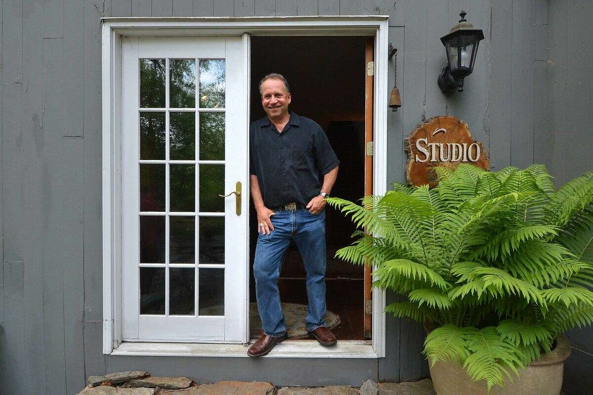 Daryl Hawk stands in the doorway of the studio at his Wilton home. His business, Hawk Photography, celebrates 30 years in business next month. Not pictured is Hawk's wife, Heidi.