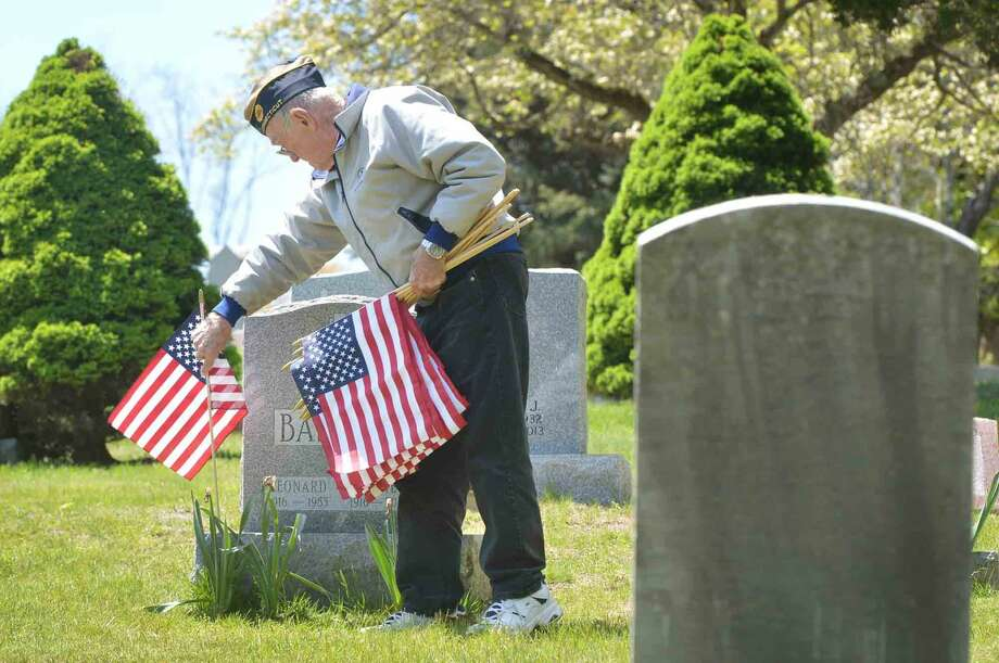American Legion Post 86 Past Commander Bing Ventres places a new American Flag on a veterans marker and removes the old ones with help from other Post 86 members, at Hillside Cemetery for Memorial Day in Wilton. The Post pays for and donates some 400 flags for Veterans in five Wilton cemeteriesin Wilton Conn. Monday May 16 2016