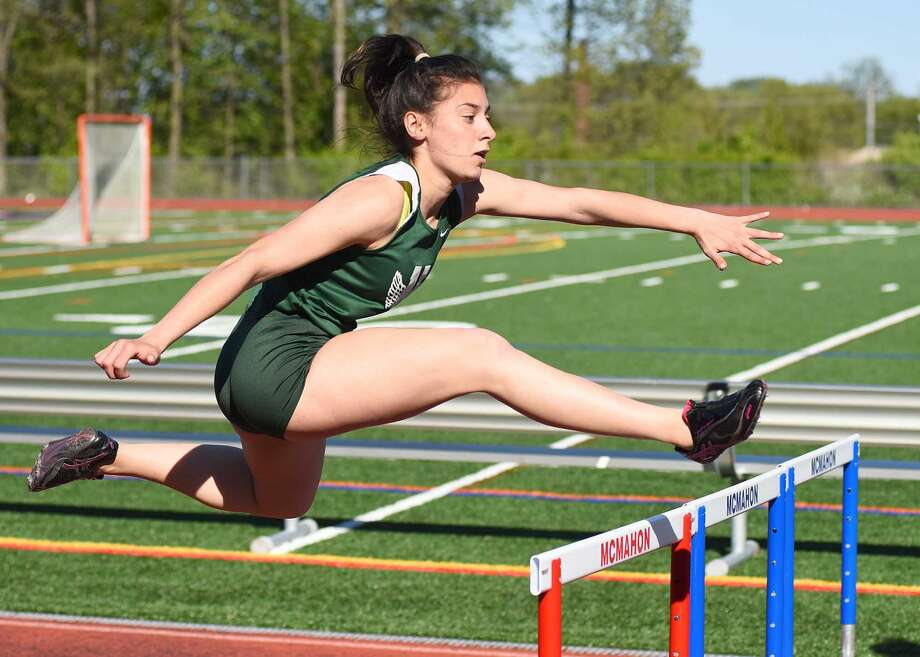 Edona Jakaj of Norwalk flies over the hurdles during the 100-meter hurdle event at Monday's dual track meet against cross-city rival Brien McMahon. The Bears edged the Senators 73-67 to clinch the city title.
