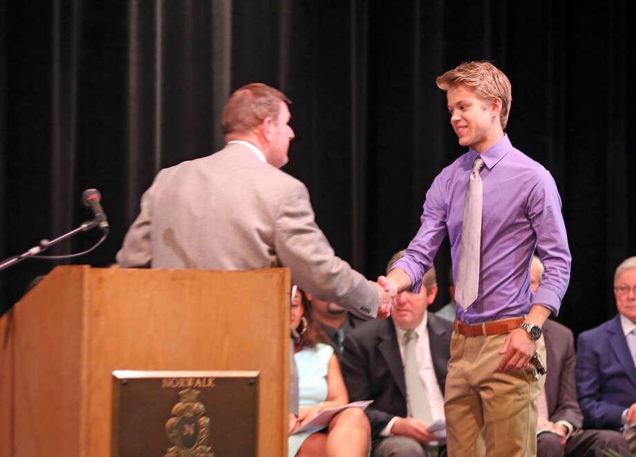Daniel Lott accepts the 2015 Boston College Scholarship during Norwalk High School's Awards Program Thursday evening. Hour Photo / Danielle Calloway