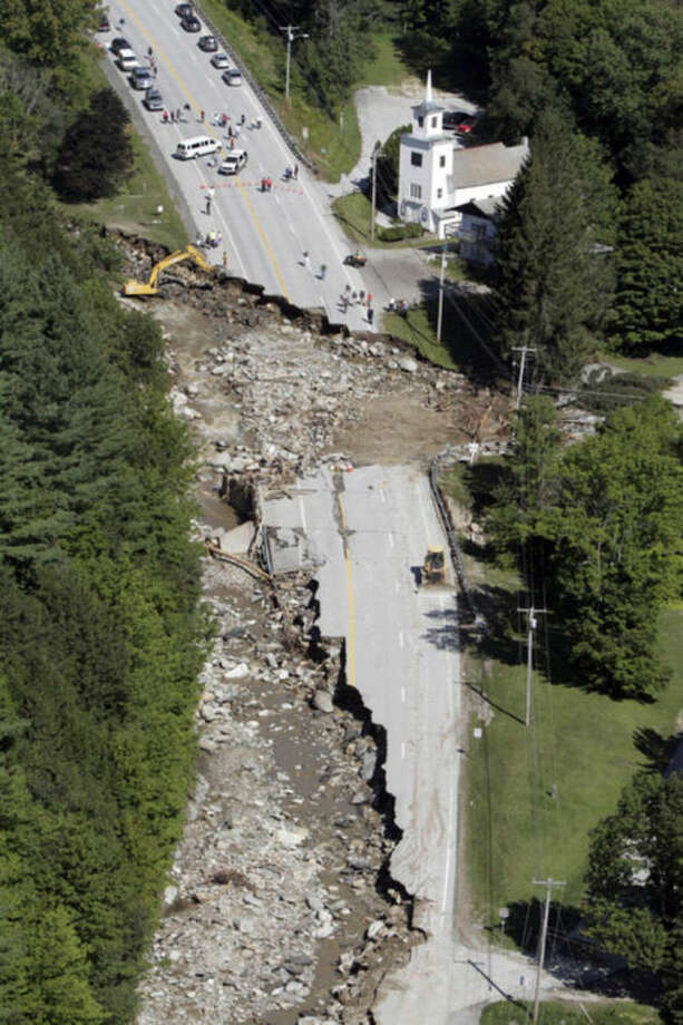 FILE -- This Aug. 30, 2011 file aerial photograph shows destruction of Route 4 in Killington, Vt., after Tropical Storm Irene passed through New England. Global warming is rapidly turning America into a stormy and dangerous place, with rising seas and disasters upending lives from flood-stricken Florida to the wildfire-ravaged West, according to a new U.S. federal scientific report released Tuesday, May 6, 2014. (AP Photo/Toby Talbot, File)